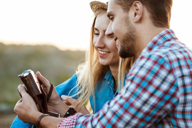 Молодая красивая пара путешественников, улыбаясь, держа старую камеру