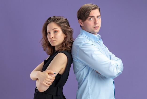 Giovane bella coppia offesa uomo e donna in piedi schiena contro schiena guardando la fotocamera durante il giorno di san valentino