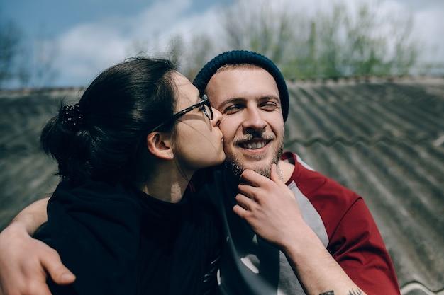家の屋根の上の若い美しいカップル