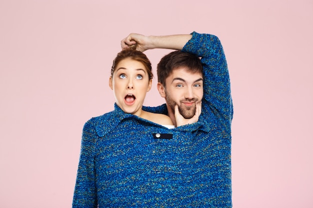 Young beautiful couple in one blue knitted sweater posing smiling having fun over light pink wall