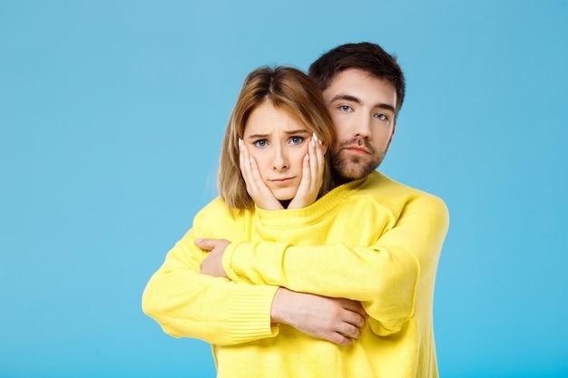 Giovani belle coppie in un maglione giallo che abbraccia sorridere sopra la parete blu