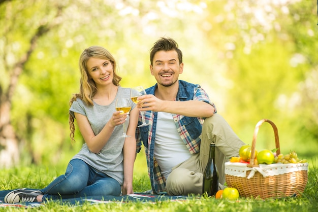 Young beautiful couple in park and drinking wine.