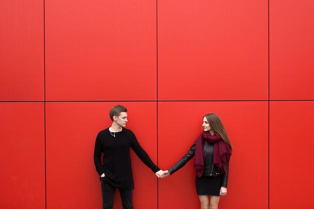 Молодая красивая пара позирует у красной стены