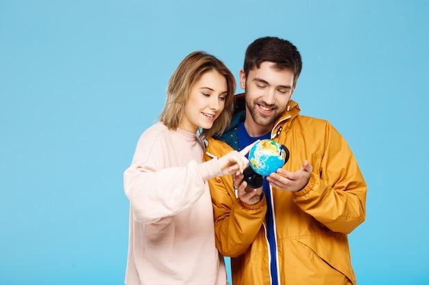 Молодая красивая пара позирует над синей стеной человек, одетый в плащ от дождя, держа маленький глобус. девушка, глядя через лупу на нем.