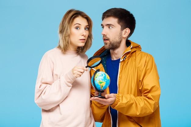 Молодая красивая пара позирует над синей стеной человек, одетый в плащ от дождя, держа маленький глобус. девушка с лупой