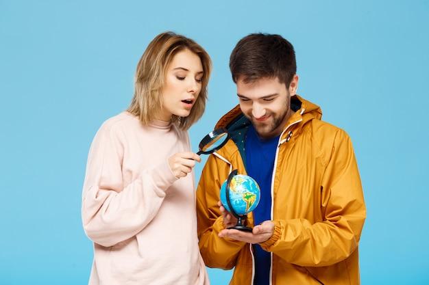 Молодая красивая пара позирует на синей стене с увеличительным стеклом и глобус