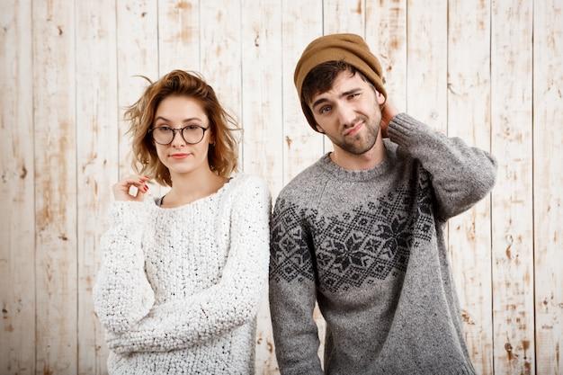 Молодая красивая пара позирует на деревянной стене