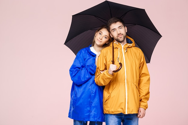 Young beautiful couple posing in rain coats holding umbrella over light pink wall
