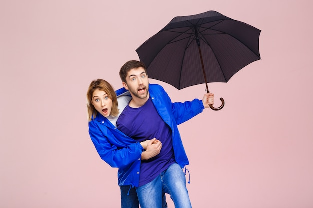 Young beautiful couple posing wearing one rain coat holding umbrella over light pink wall