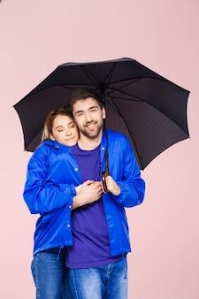 Молодая красивая пара позирует носить один плащ с зонтиком над светло-розовой стеной