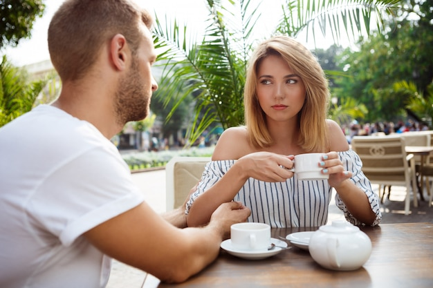 Young beautiful couple quarreling, sitting in cafe.