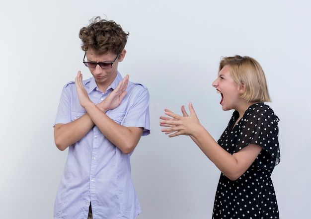 Giovane bella coppia che litiga donna che grida sul suo fidanzato che mostra il gesto di arresto con la faccia imbrunita sul muro bianco