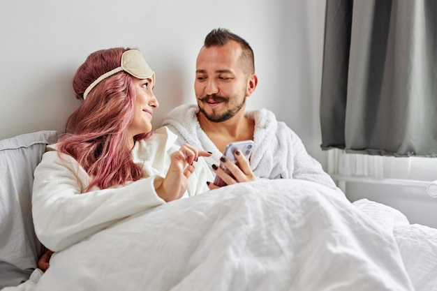 Young beautiful couple relaxing in bed using cell phones in the morning