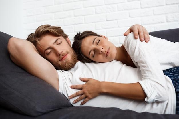 Лежать молодых красивых пар расслабляющий лежа на софе дома.