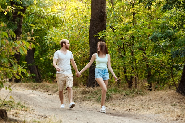 Young beautiful couple resting, walking in park, smiling, rejoicing.