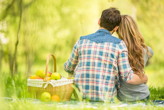 Young beautiful couple on romantic picnic in summer park.
