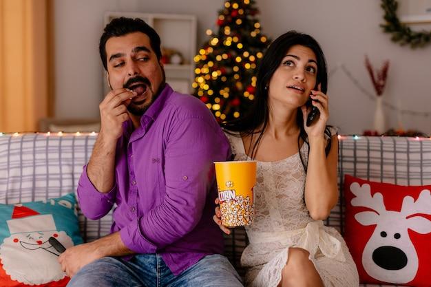 Giovane e bella coppia seduta su un divano uomo mangia popcorn dal secchio mentre la sua ragazza parla al cellulare in camera decorata con albero di natale in background