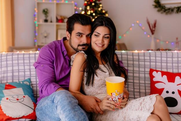 Giovane e bella coppia seduta su un divano uomo e donna con un secchio di popcorn guardando la tv insieme felici innamorati in una stanza decorata con albero di natale sullo sfondo