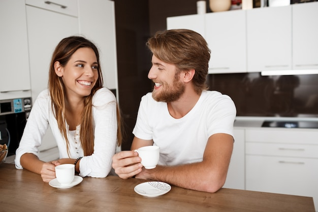 Young beautiful couple sitting at kitchen drinking morning coffee smiling.