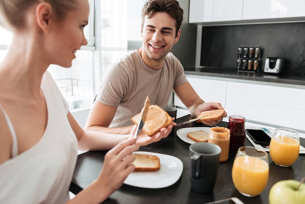Young beautiful couple sitting in kitchen and have breakfast