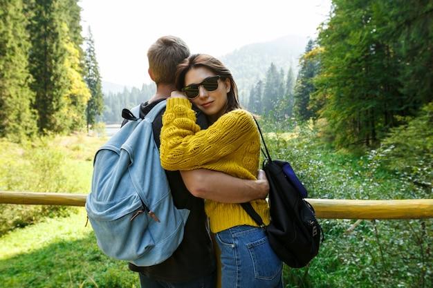 Young beautiful couple smiling, embracing, enjoying mountains lanscape
