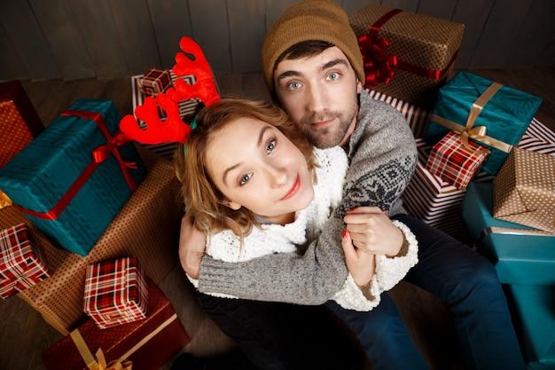 Young beautiful couple smiling embracing sitting among christmas gift boxes.