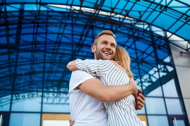 Молодая красивая пара улыбаясь, обнимая, гуляя по городу.