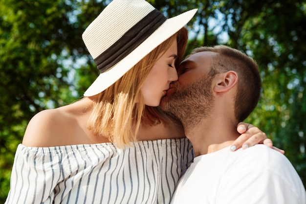 Young beautiful couple smiling, kissing, embracing, walking in park.