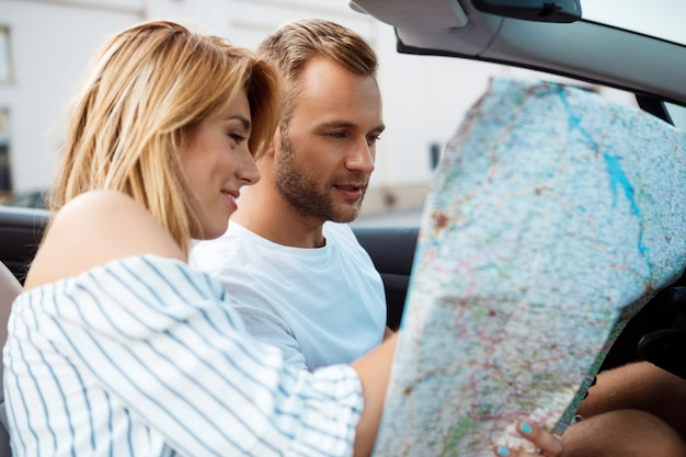 Young beautiful couple smiling, looking at map, sitting in car.