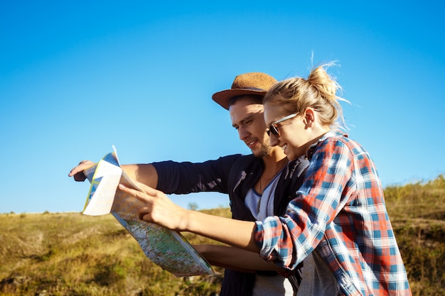 Young beautiful couple smiling, looking for route on map