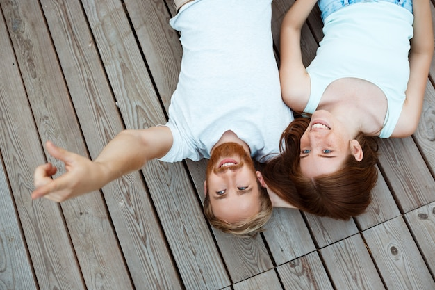 Young beautiful couple smiling, lying on wooden boards