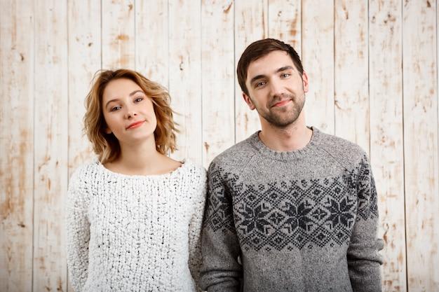 Молодая красивая пара, улыбаясь на деревянной стене