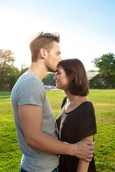 Молодая красивая пара, улыбаясь, отдыхая, целуя в парке