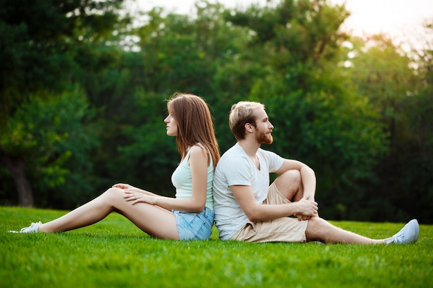 Young beautiful couple smiling, sitting on grass in park.