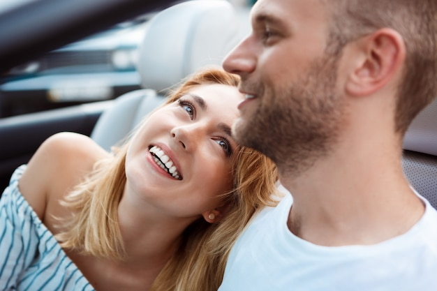 Молодая красивая пара улыбаясь, сидя в машине возле моря.