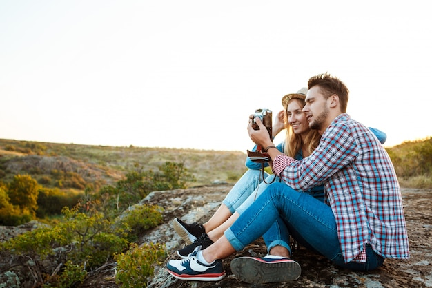 Young beautiful couple smiling, taking picture of canyon landscape