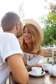 Young beautiful couple speaking, smiling, resting in cafe.