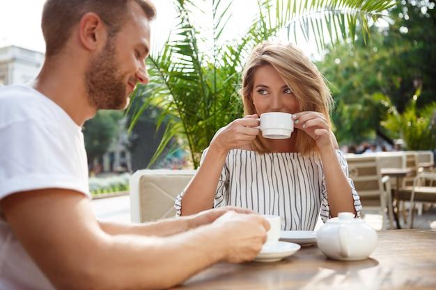 Молодая красивая пара, выступая, улыбаясь, отдыхая в кафе.