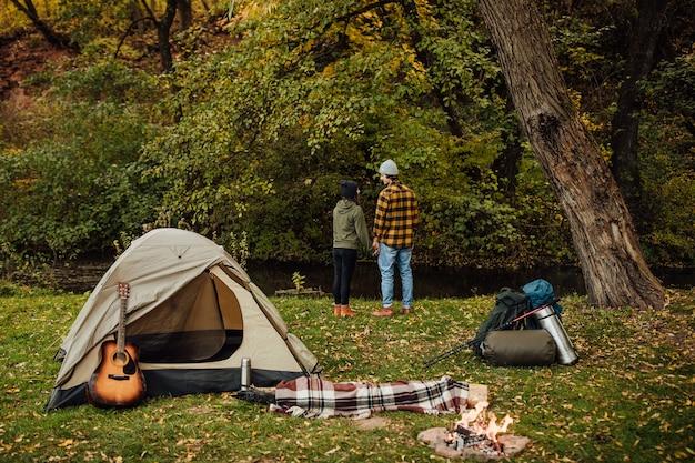 キャンプに立っている若い美しいカップル