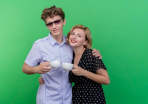 緑の壁に恋をして幸せな笑顔のコーヒーカップを持って一緒に立っている若い美しいカップル