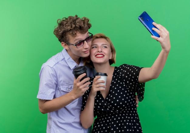 緑の壁に笑みを浮かべて自分撮りをしながら携帯電話を使用してコーヒーカップを持って一緒に立っている若い美しいカップル