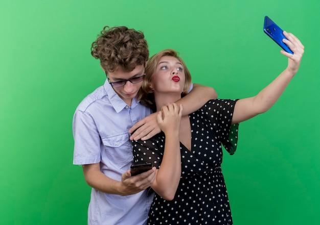 녹색 벽에 키스를 불고 셀카 복용 휴대 전화를 사용하여 함께 서있는 젊은 아름다운 부부