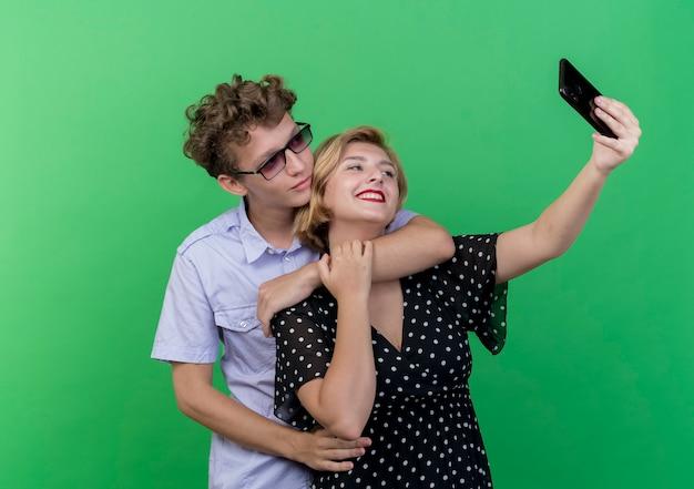 Giovani belle coppie che stanno insieme facendo uso del telefono cellulare che prende selfie che sorride sopra la parete verde