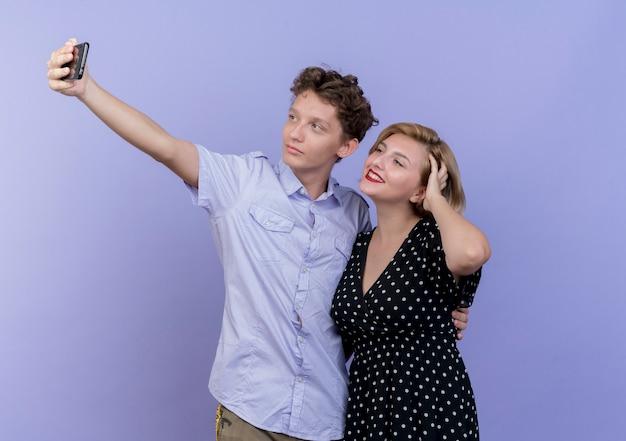 파란색 벽 위에 미소를 셀카 복용 휴대 전화를 사용하여 함께 서있는 젊은 아름다운 부부
