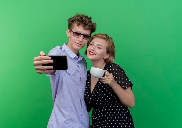 녹색 벽 위에 미소를 셀카 복용 휴대 전화를 사용하여 함께 서있는 젊은 아름다운 부부