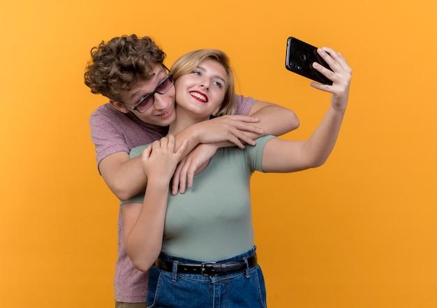오렌지 벽 위에 미소를 셀카 복용 휴대 전화를 사용하여 함께 서 젊은 아름 다운 부부