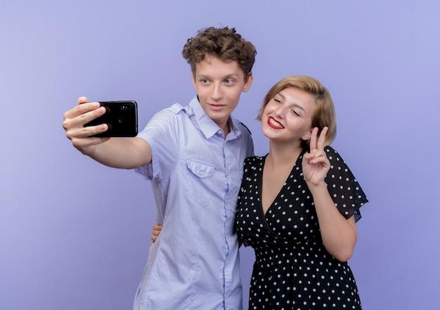 Giovane bella coppia in piedi insieme utilizzando il telefono cellulare prendendo selfie sorridente che mostra v-segno oltre la parete blu