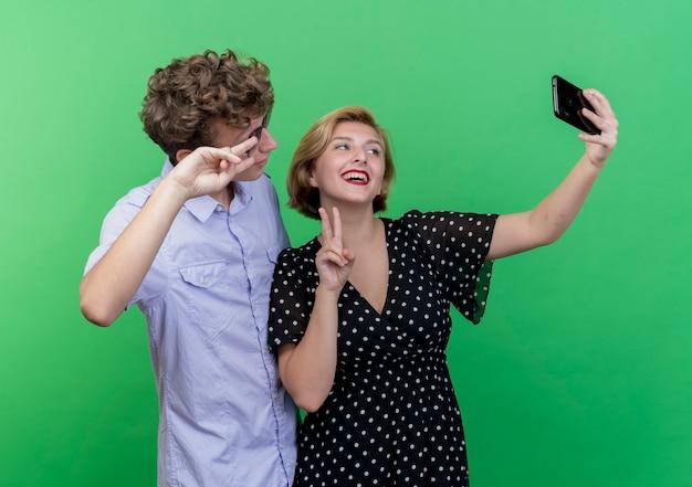 녹색 벽 위에 v 기호를 보여주는 미소 셀카 복용 휴대 전화를 사용하여 함께 서 젊은 아름 다운 부부