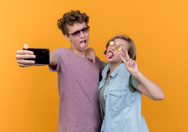 携帯電話を使用して一緒に立っている若い美しいカップルは、舌を突き出して、オレンジ色の壁にvサインを見せて笑顔で自分撮りを取ります