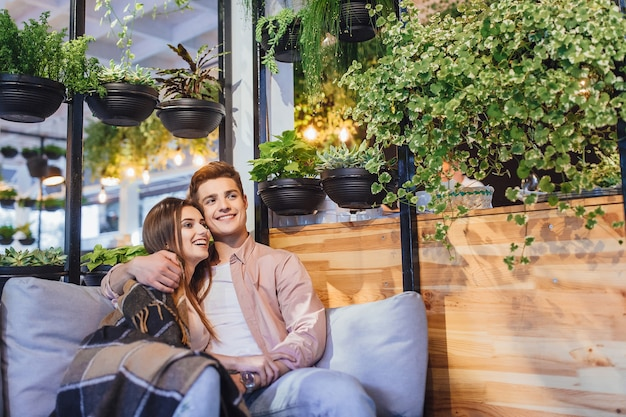 Young beautiful couple on the summer terrace! the guy and the girl are hugging in the cafe.